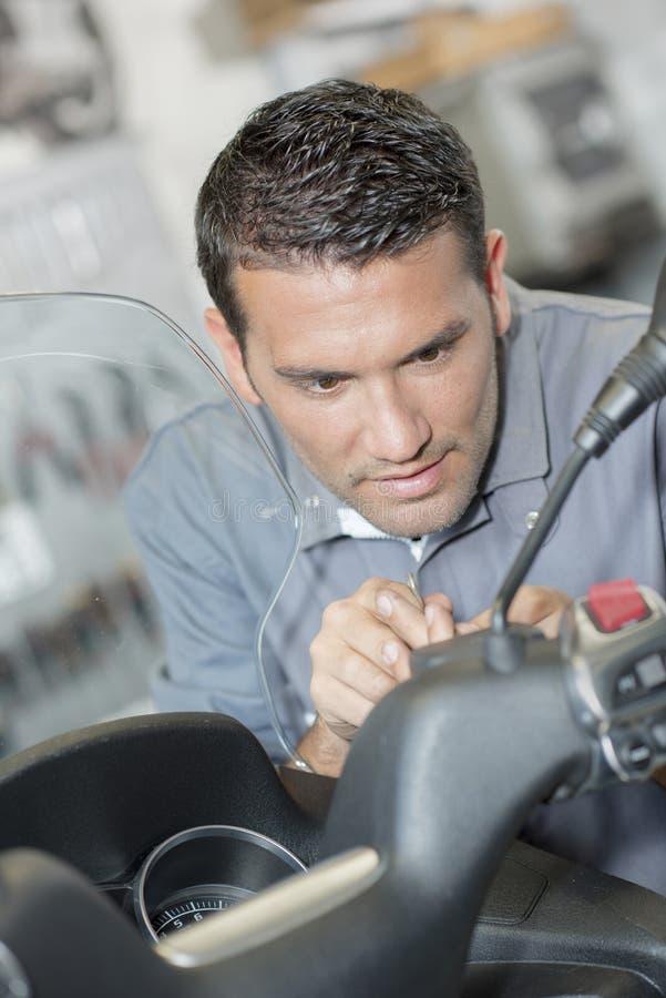 Mechanic repairing handlebars scooter. Mechanic repairing handlebars of scooter stock photography
