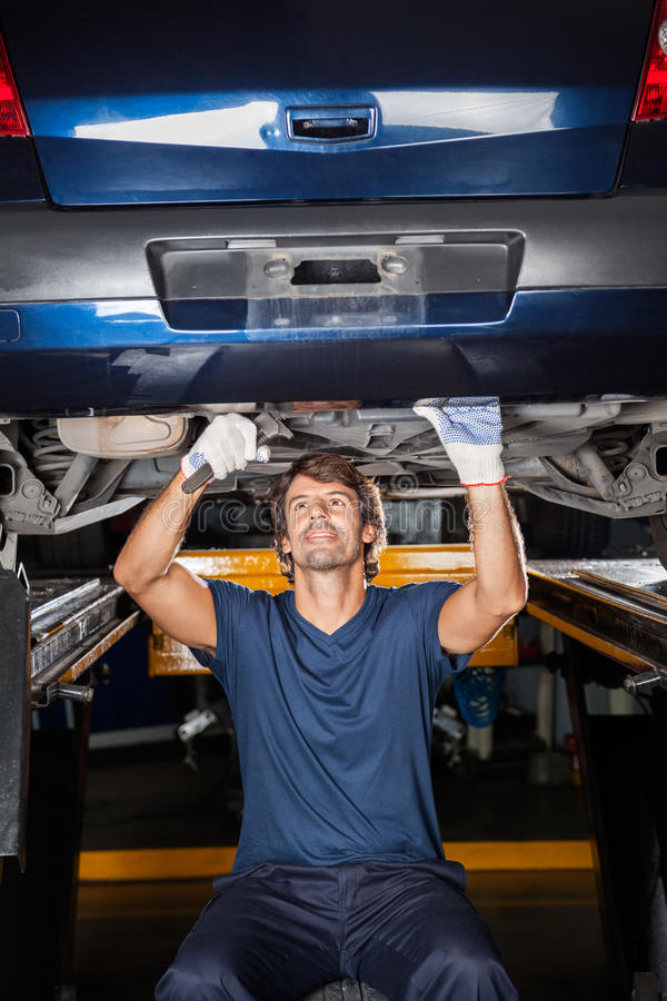 Mechanic Repairing Underneath Car stock images