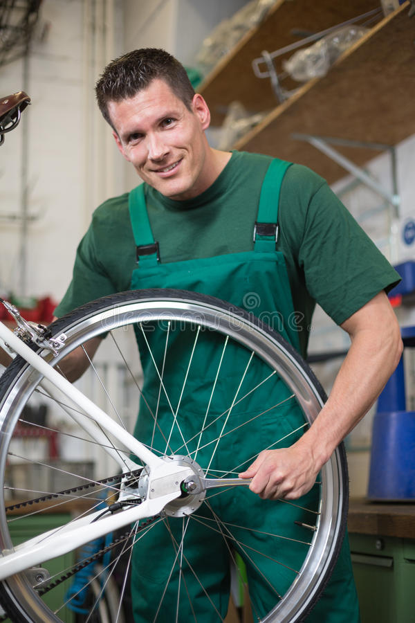 Mechanic repairing wheel on a bicycle in workshop. Mechanic or serviceman installing wheel on a bicycle in workshop royalty free stock photos