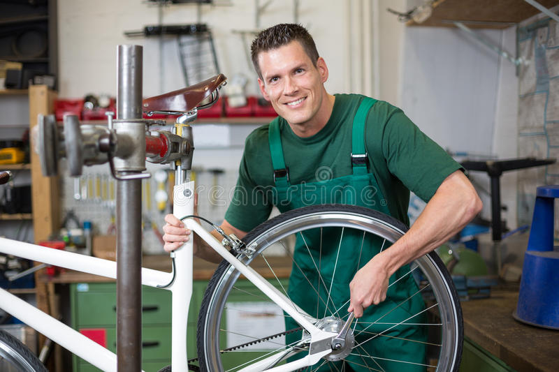Mechanic repairing wheel on a bicycle in workshop. Mechanic or serviceman installing wheel on a bicycle in workshop royalty free stock photography