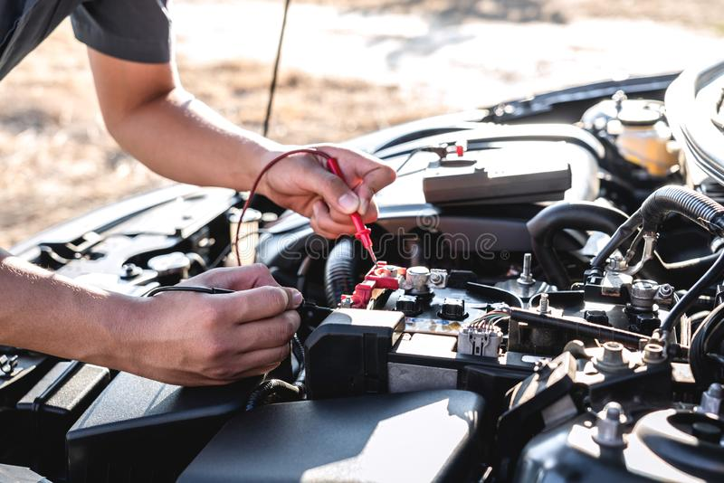 Mechanic repairman checking engine automotive in auto repair service and using digital multimeter testing battery to measure stock photography