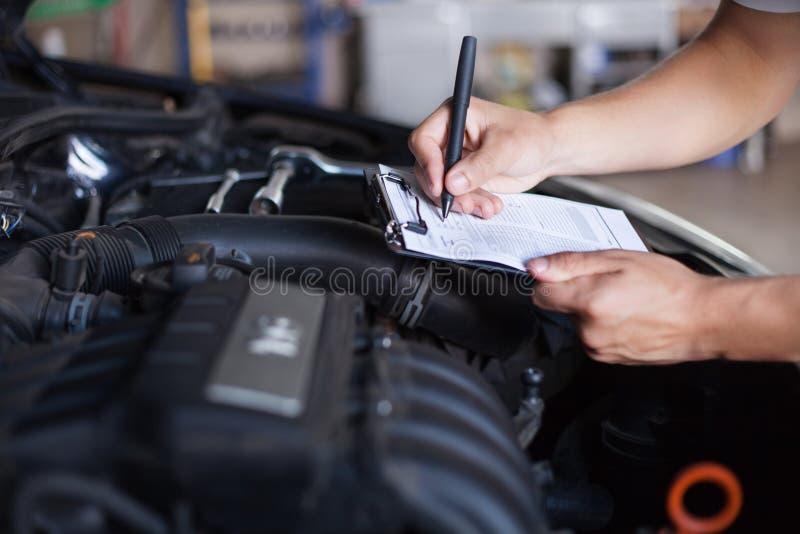 Mechanic repairman inspecting car stock image