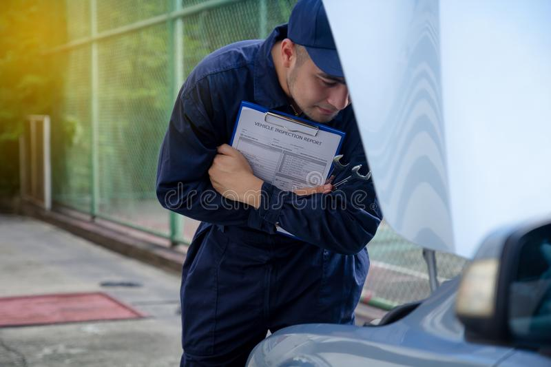 Mechanic repairman inspecting car, Maintaining car records. royalty free stock images