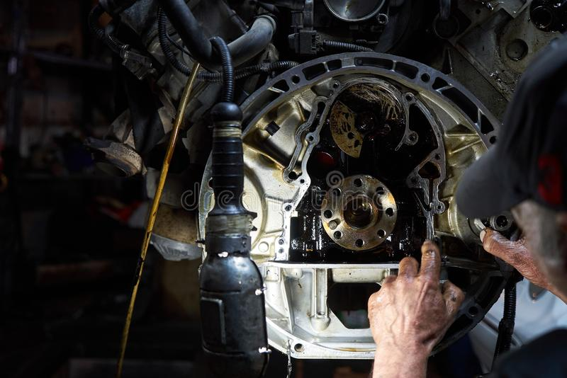 Mechanic repairman working and repair car engine in car service. Centre, close-up. Man hand technician checking or fixing the engine part royalty free stock images