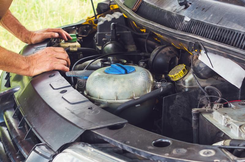 The mechanic`s hands performing a car engine check stock photos