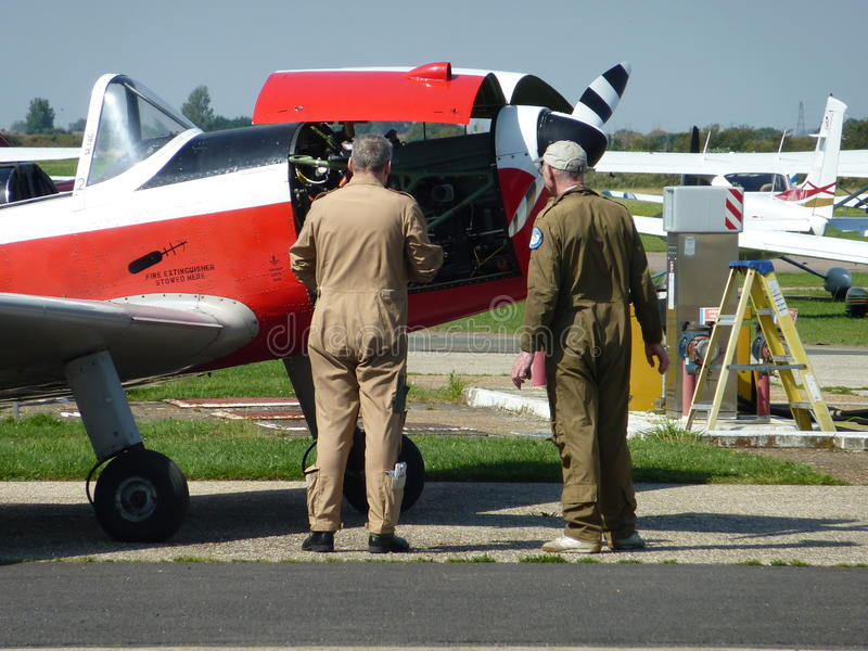 Plane mechanics. Two mechanics working on the engine of a light aircraft stock images