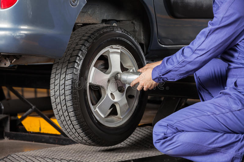 Mechanic Screwing Tire With Pneumatic Wrench. Midsection of male mechanic screwing car tire with pneumatic wrench at garage royalty free stock image