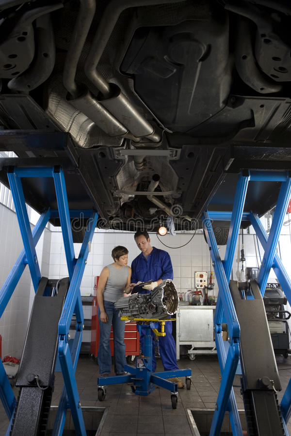 Mechanic showing clipboard to woman by elevated car, low angle view. Mechanic showing clipboard to women by elevated car, low angle view stock image