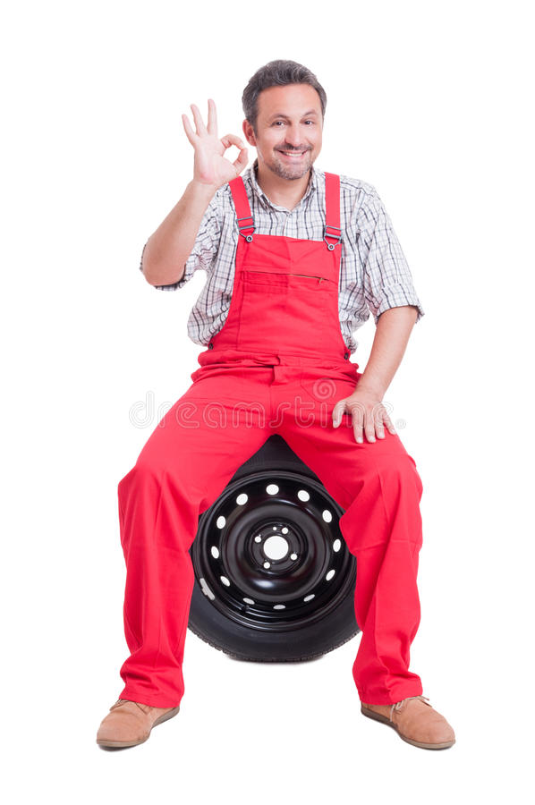 Mechanic showing good or perfect sign gesture. Sitting on tire isolated on white stock photo