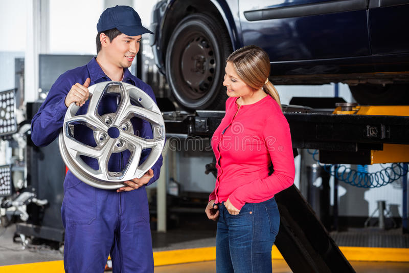 Mechanic Showing Hubcap To Customer. Male mechanic showing metallic hubcap to female customer at garage stock image