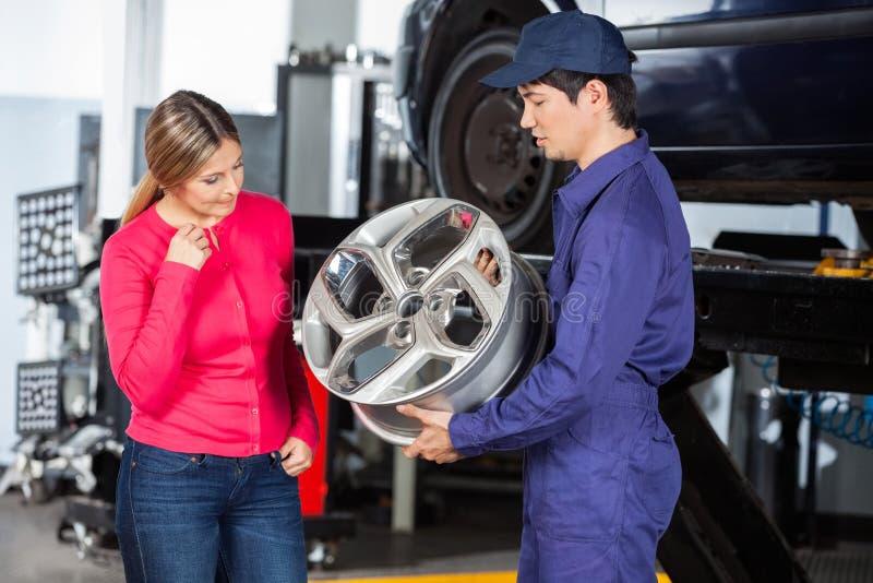 Mechanic Showing Hubcap To Customer. Male technician showing metallic hubcap to female customer at garage stock photography