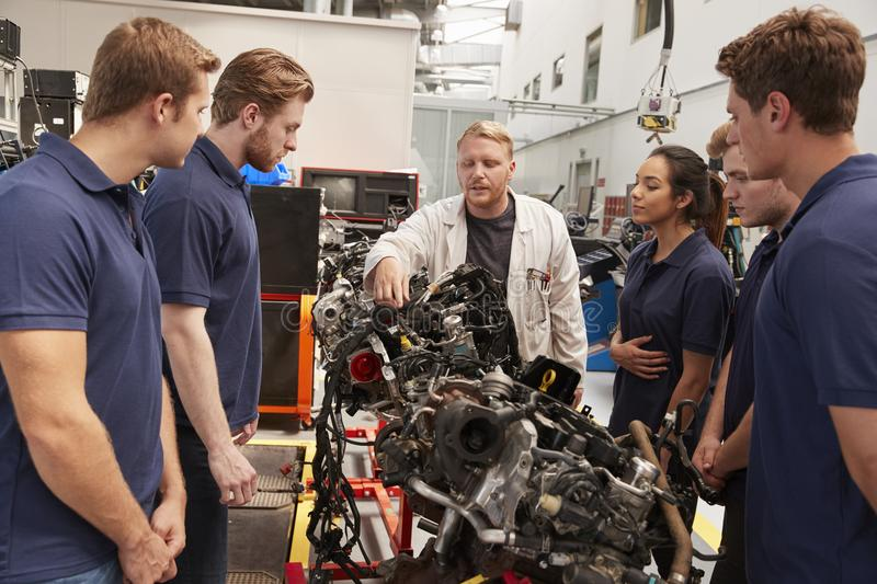 Mechanic showing parts of an engine to apprentices, close up stock photo