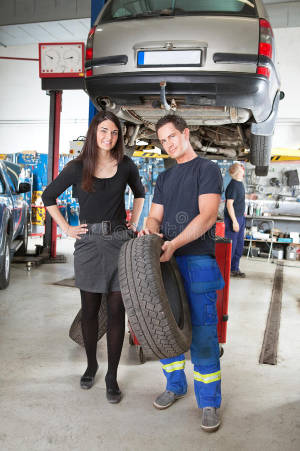 Download Mechanic Showing Tire To Customer Stock Photo - Image: 20298680