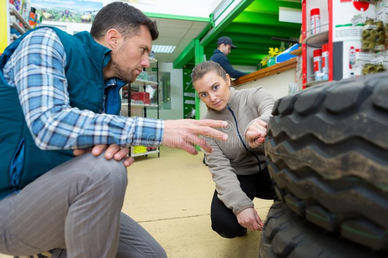 Mechanic showing tread tire to female colleague royalty free stock photography