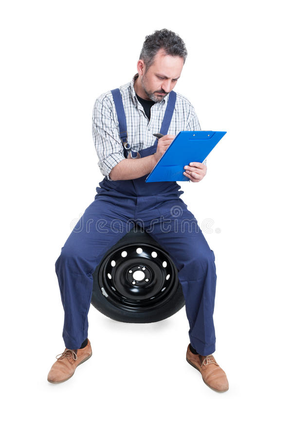 Mechanic sitting on wheel and writing on checklist stock photo