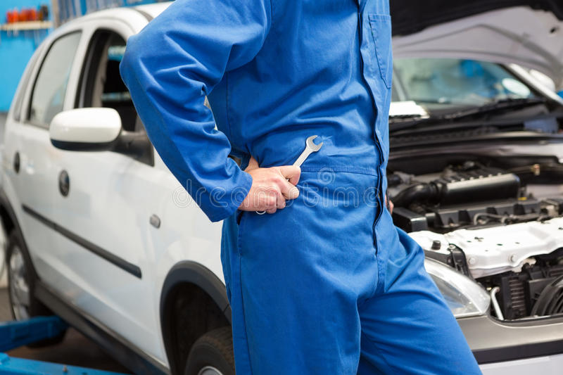 Mechanic with spanner by car. Male mechanic with spanner leaning on car royalty free stock images