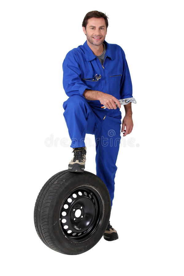 Mechanic with a spare tyre royalty free stock photos