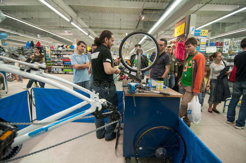 Mechanic teaching people how to true a bike wheel on a truing stand stock image