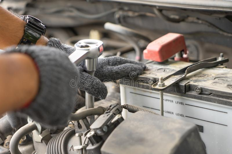 Mechanic, technician man check the car engine in garage. Car service, repair, fixing, checking maintenance working with socket. Wrench at workshop. Inspection royalty free stock photo