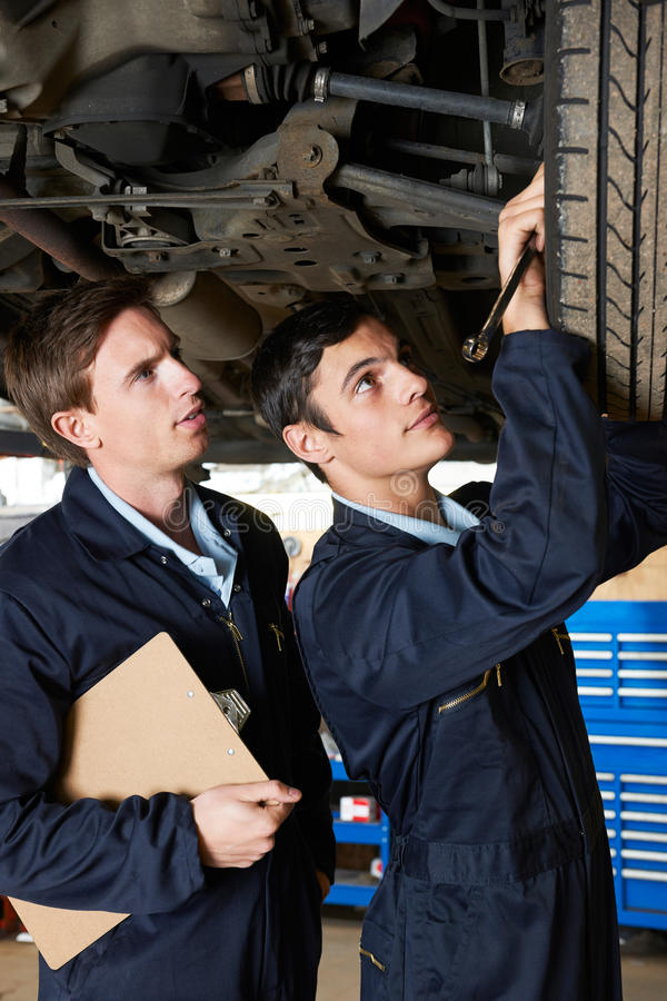 Mechanic And Trainee Working Under Car stock images