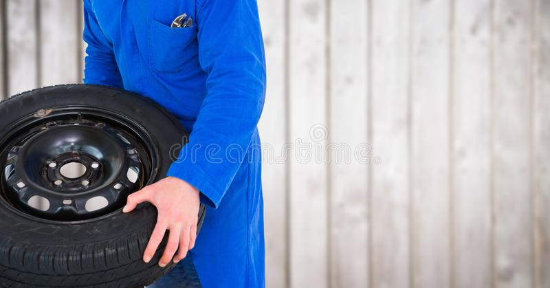 Mechanic with tyre against blurry wood panel. Digital composite of Mechanic with tyre against blurry wood panel royalty free stock image