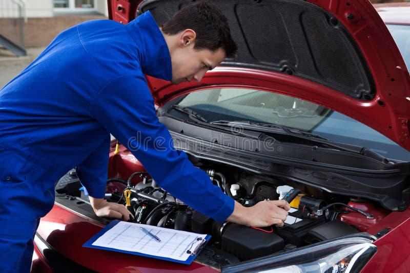 Mechanic in uniform repairing car royalty free stock photos