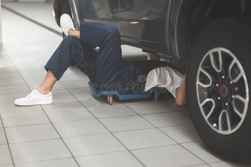 Mechanic in uniform working in car service department fixing vehicle chassis.  royalty free stock photos