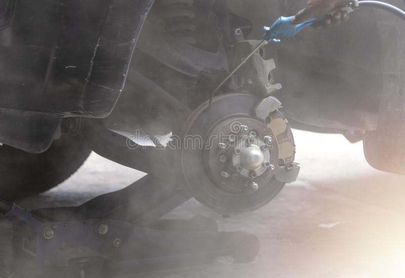 Mechanic use air gun clean disc break take dust removes before change break pat. Transportation concept. Mechanic use air gun clean disc break take dust removes stock photos
