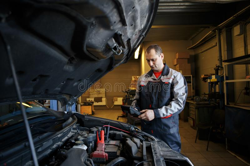 Mechanic using booster cables to start-up a car engine stock image