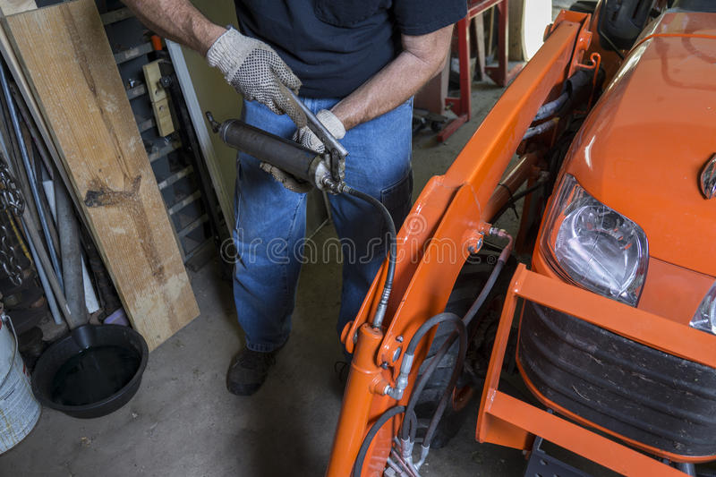 Mechanic Using A Grease Gun. To lube a tractor stock image