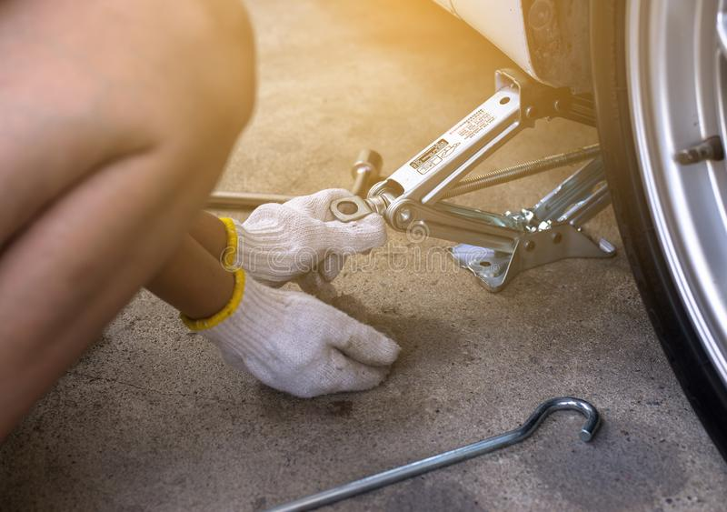 Mechanic using jack for car lifting,changing car tire royalty free stock photography