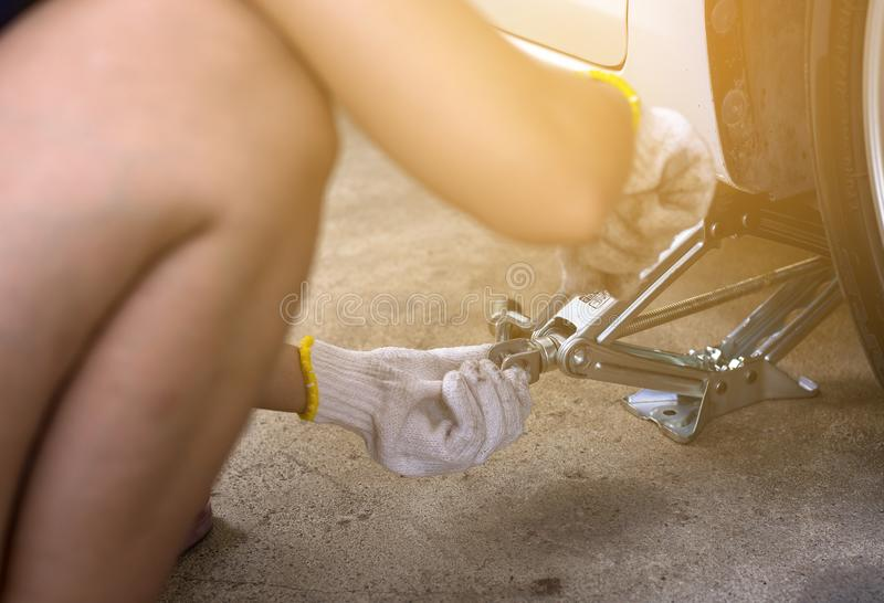 Mechanic using jack for car lifting,changing car tire royalty free stock photo