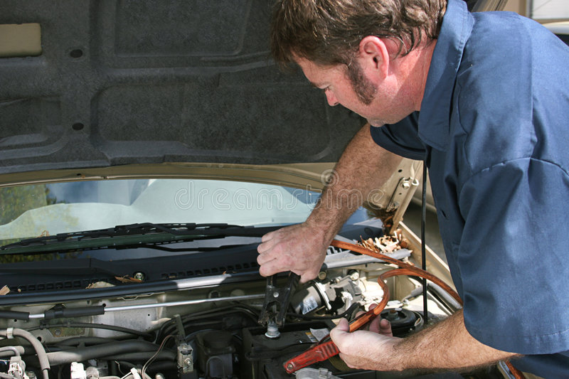Mechanic Using Jumper Cables. An auto mechanic using jumper cables on a car battery. Horizontal with copy space for text stock photos