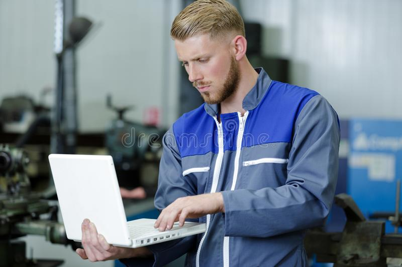 Mechanic using laptop for checking car engine royalty free stock photos
