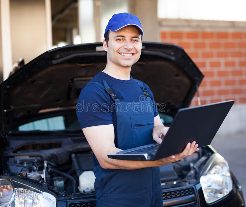 Mechanic using a laptop computer to check a car engine stock photos
