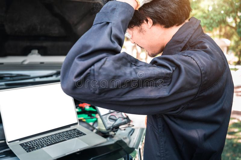 Mechanic Using Laptop While Examining Car Engine, pointing in blank screen stock photo