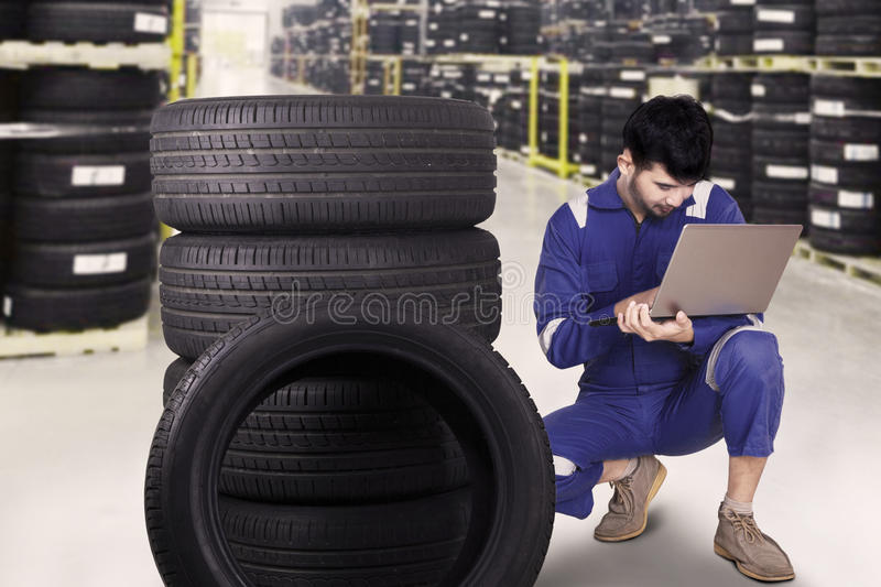 Mechanic using a laptop to check tires stock image