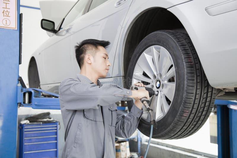 Mechanic Using Power Tool on Car Wheel royalty free stock image