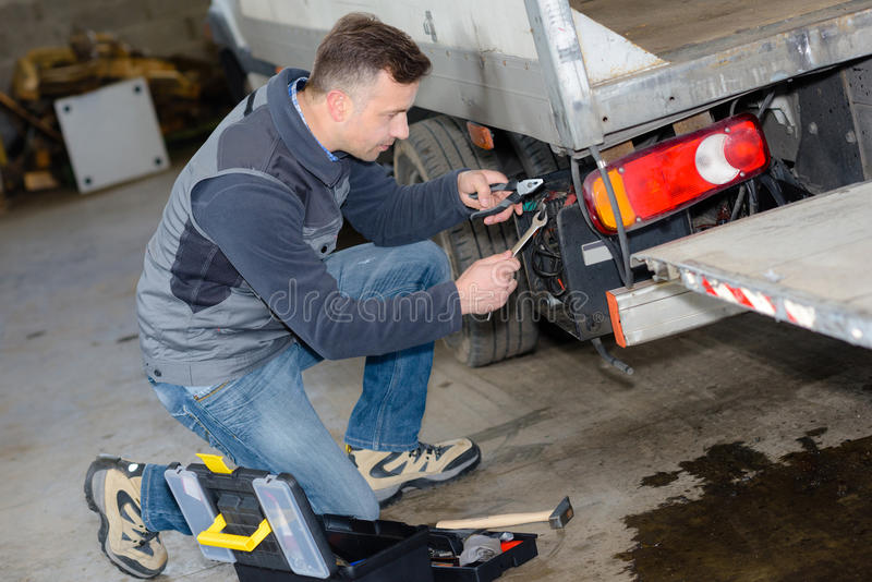 Mechanic using screwdriver on truck at repair garage royalty free stock photos
