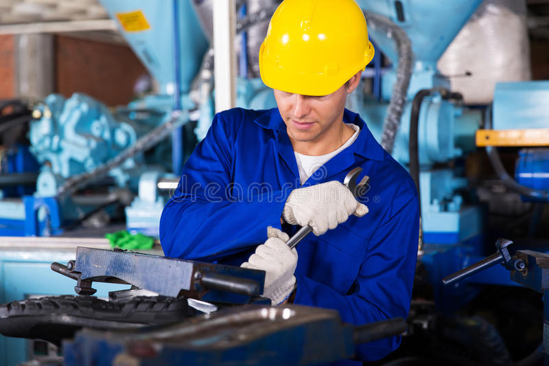 Mechanic using spanner. Skilled factory mechanic using spanner fasten gumboot making machine stock photos