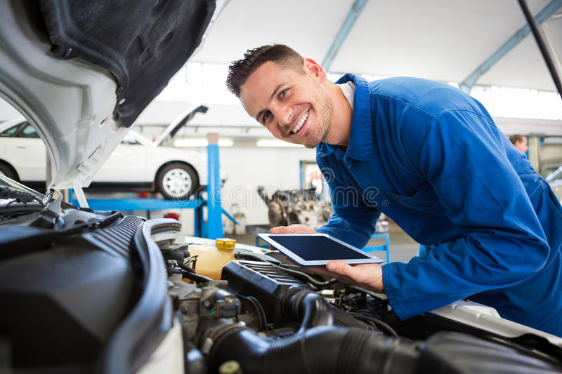 Mechanic using tablet on car stock images