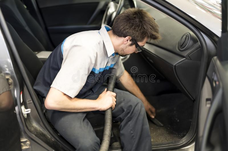 Mechanic vacuuming the car at the garage stock photos