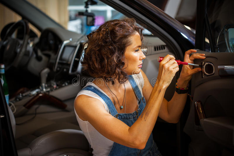 Mechanic woman in a blue overalls repair the door of car royalty free stock image