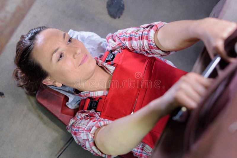 Mechanic woman underneath car checking car conditions stock photos