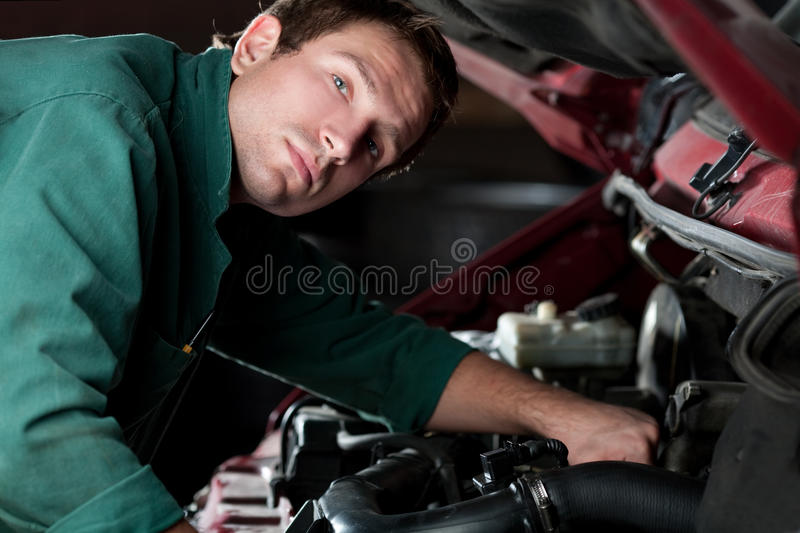 Mechanic at work fixing auto in auto service royalty free stock photography
