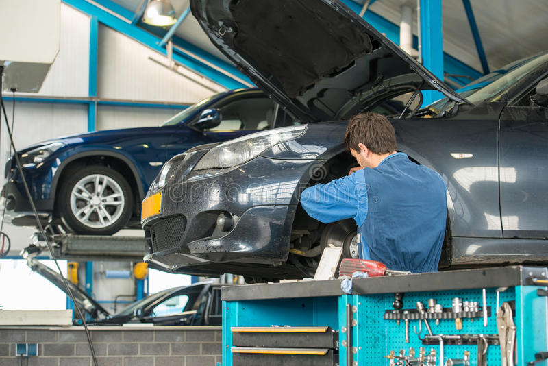 Mechanic at work in a garage. Mechanic, at work on the wheel hub and brake disk of a car in a garage, with other vehicles on car lifts in the background and a royalty free stock photo
