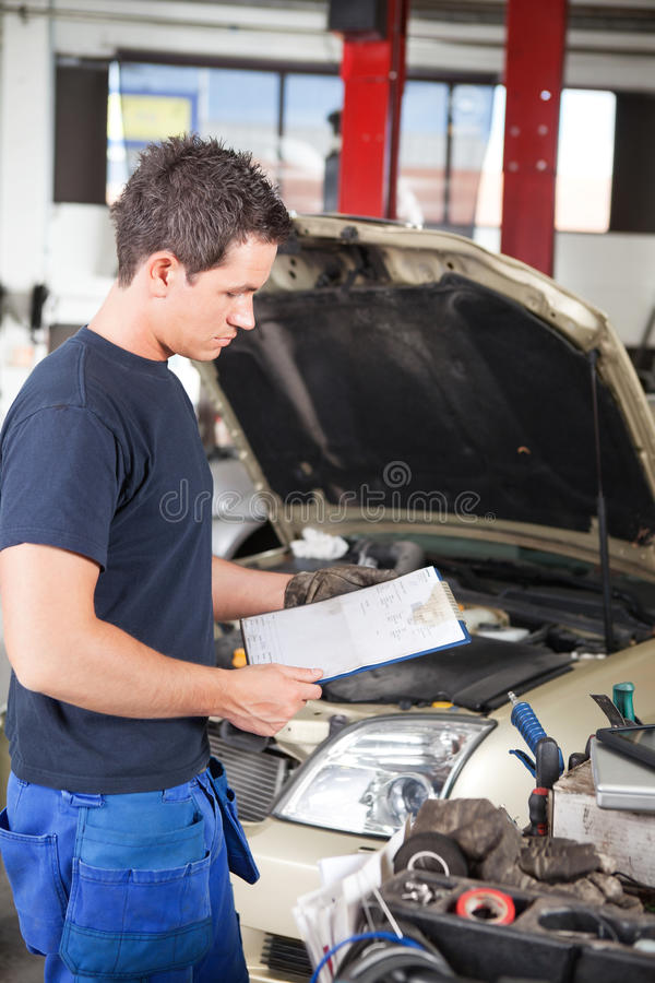 Mechanic with Work Order. Three-quarter length of mechanic holding a work order royalty free stock image