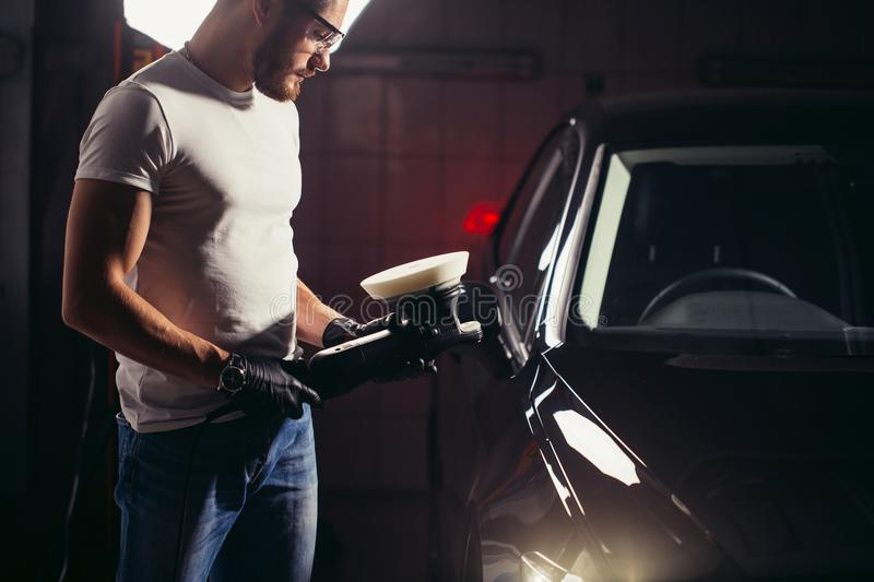 Mechanic worker prepare for polishing car by power buffer machine royalty free stock photography