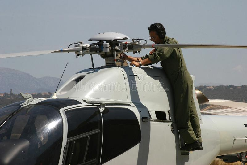 Mechanic working on ASPA eurocopter acrobatic helicopters before airshow wide stock image