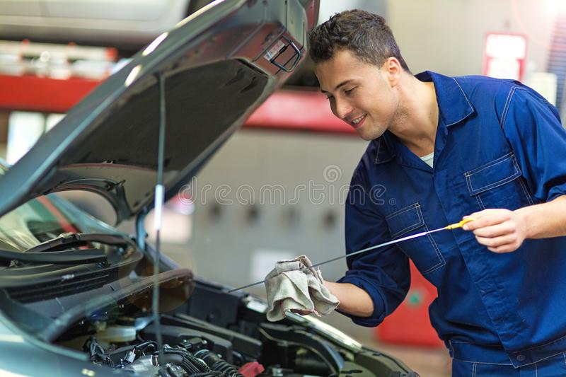 Car mechanic working on a car. Mechanic working on car in auto repair shop royalty free stock photos